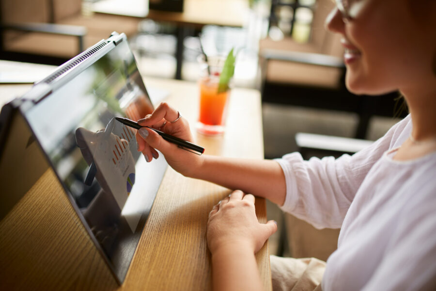Businesswoman hand pointing with stylus on the chart over convertible laptop screen in tent mode. Woman using 2 in 1 notebook with touchscreen for work on business presentation.